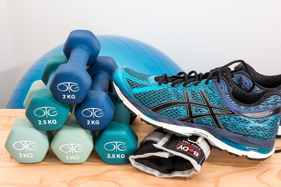 Stack of shoes, weights, and other workout equipment