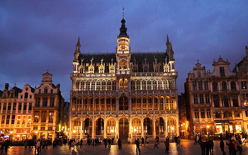 Image of an iconic building in Brussels, Belgium lit up at night.