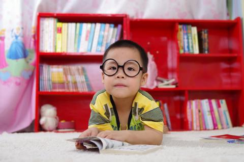 Young child wearing glasses sitting in front of a red bookshelf