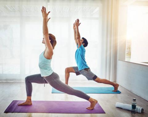 Man and woman in profile standing on Yoga mats in a standing Yoga pose.