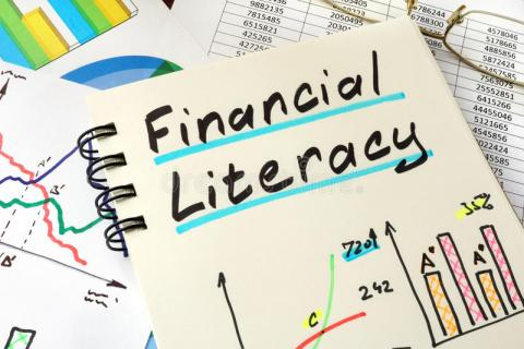 "Image of a notepad with the words ""Financial Literacy"" written out and underlined. There are some graphs drawn on the paper and the notebook is sitting on top of other papers with graphs and numbers."