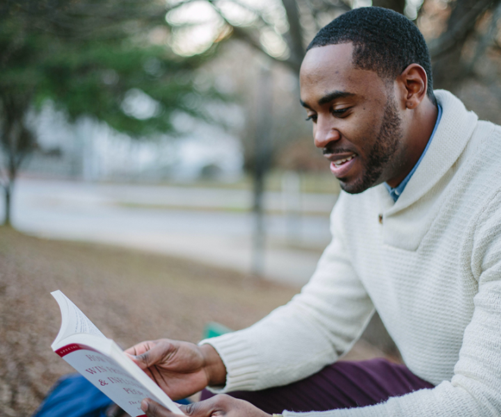 Man in sweater reading book outdoors